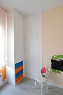 Armario a medida de dos cuerpos con cajones en colores, uno de ellos empotrado en un hueco de la pared