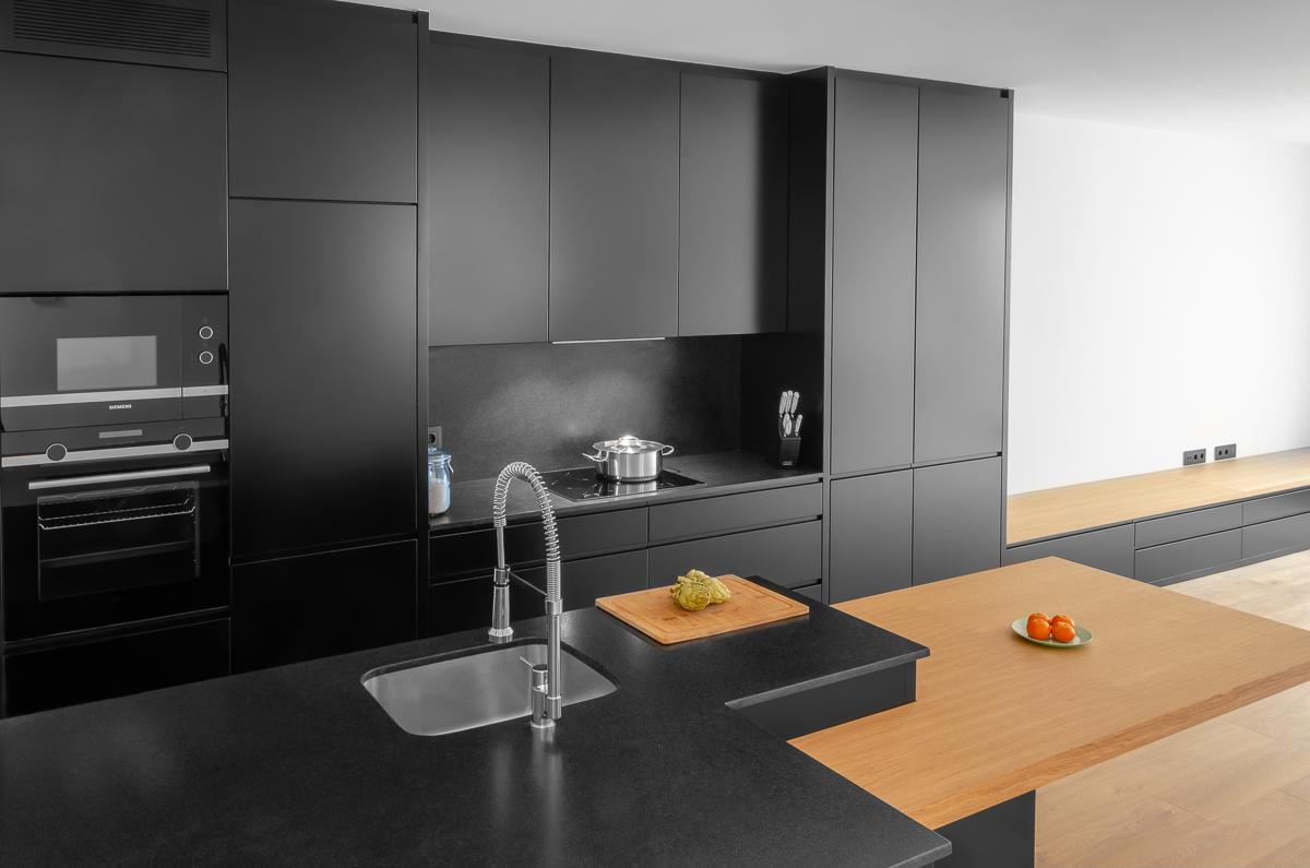 Cocina de color negro con isla negra y mesa de roble Barcelona