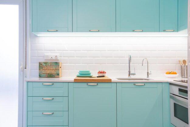 Muebles de cocina color aguamarina y azulejos blancos