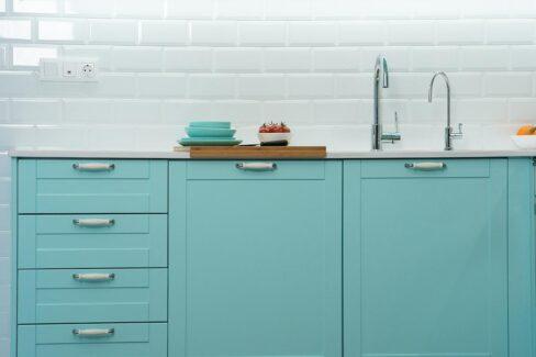 Muebles de cocina aguamarina y paredes blancas